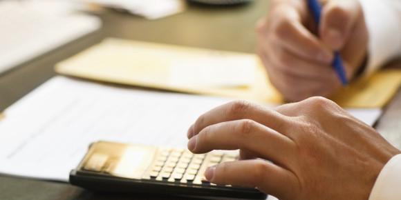 Businessman using calculator at office desk